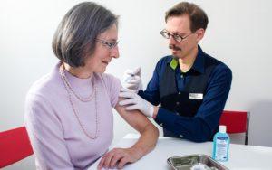 Apotheker Martin Affentranger impft eine Kundin im Sprechzimmer